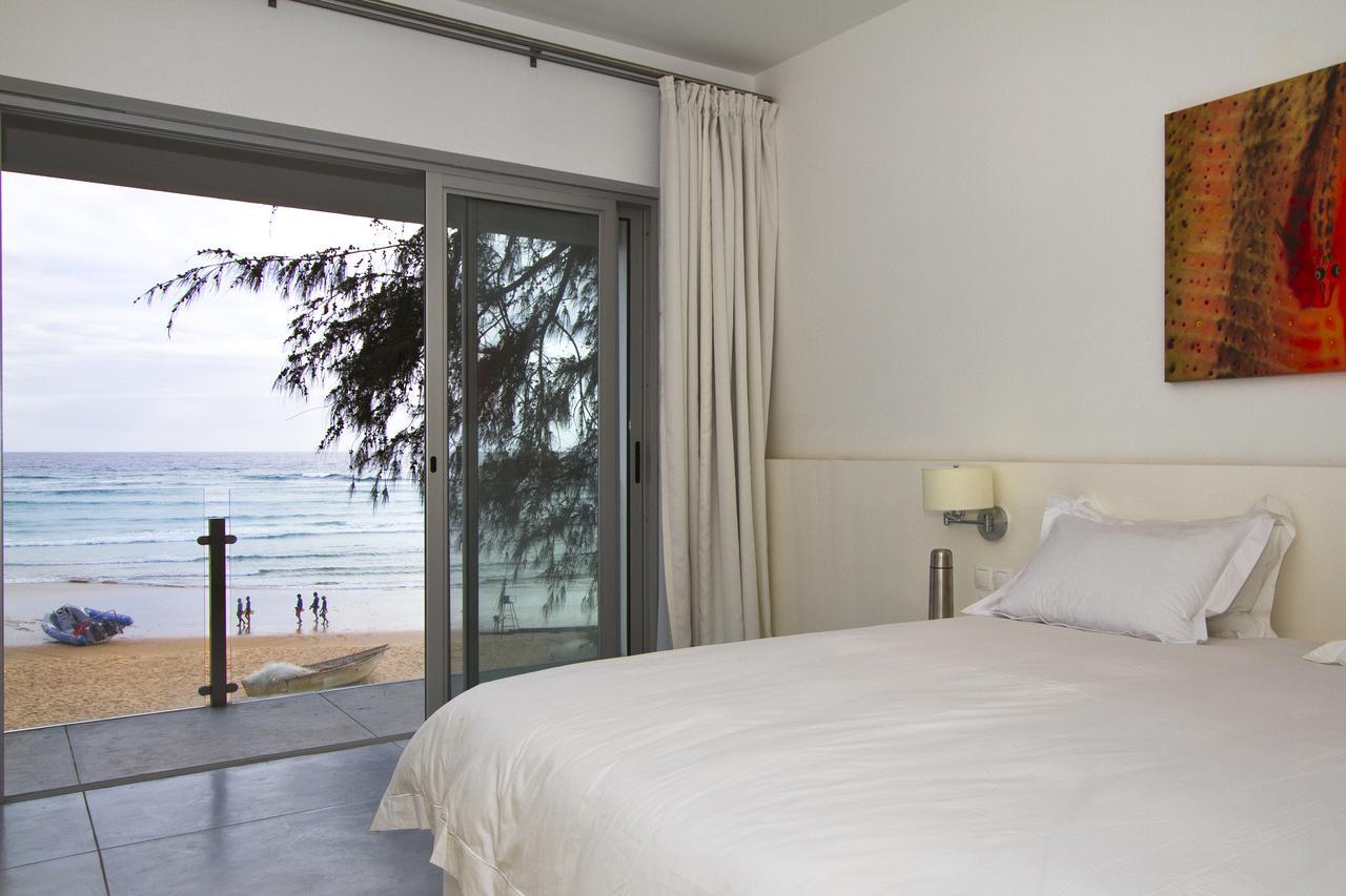 foto do quarto do hotel tofo mar mostrando vista da praia pela janela em moçambique